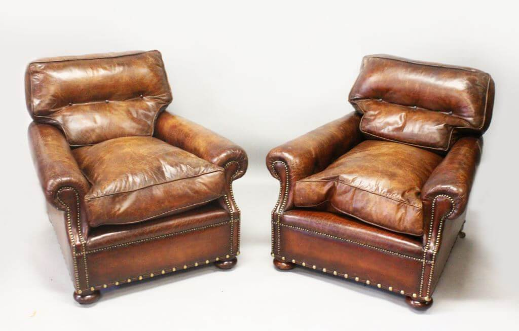 A good pair of brown leather club armchairs, with button upholstered backs,/Auctioneers and Valuers