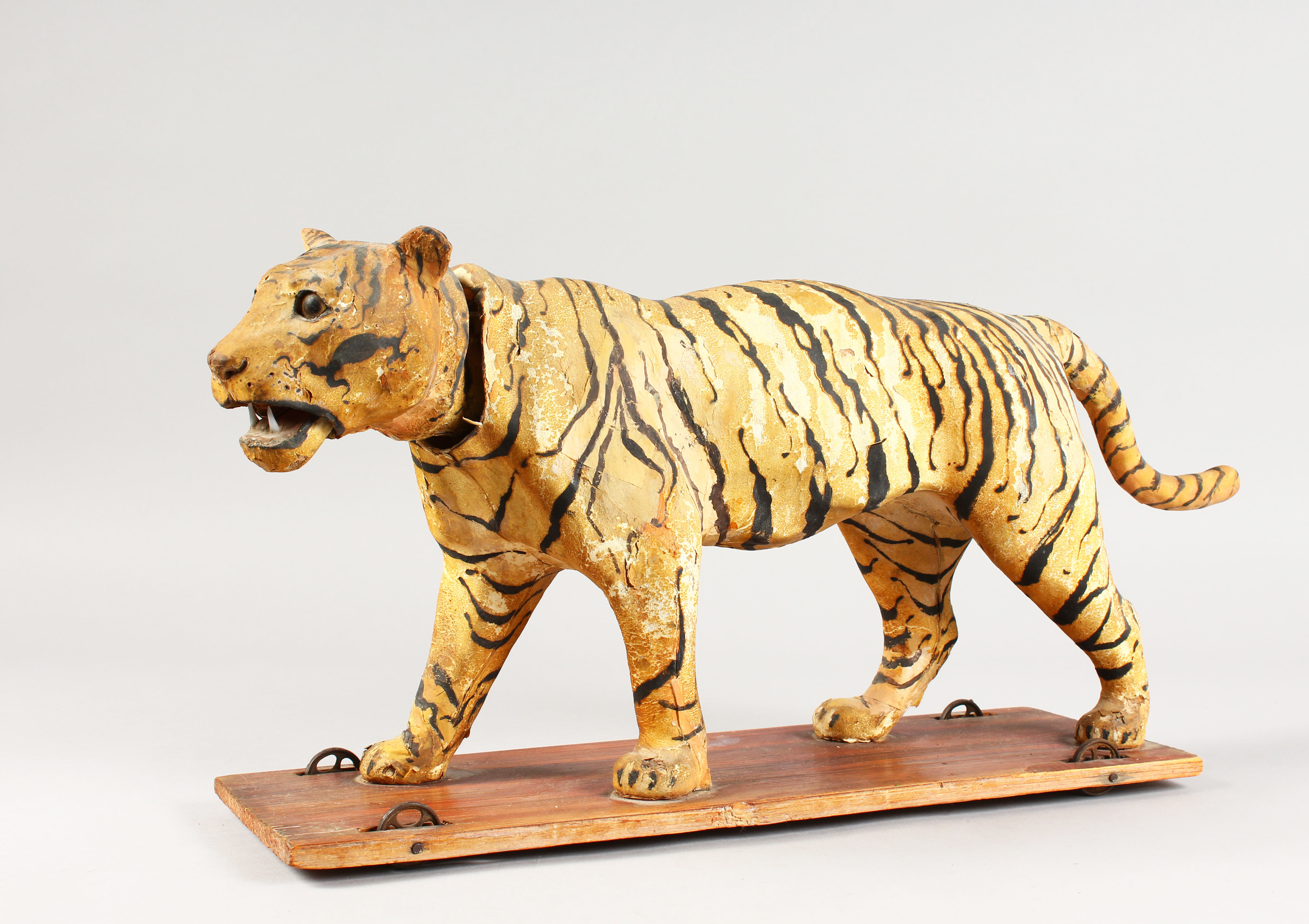 A Victorian automated Tiger with nodding head on a wooden base with wheels./Auctioneers and Valuers