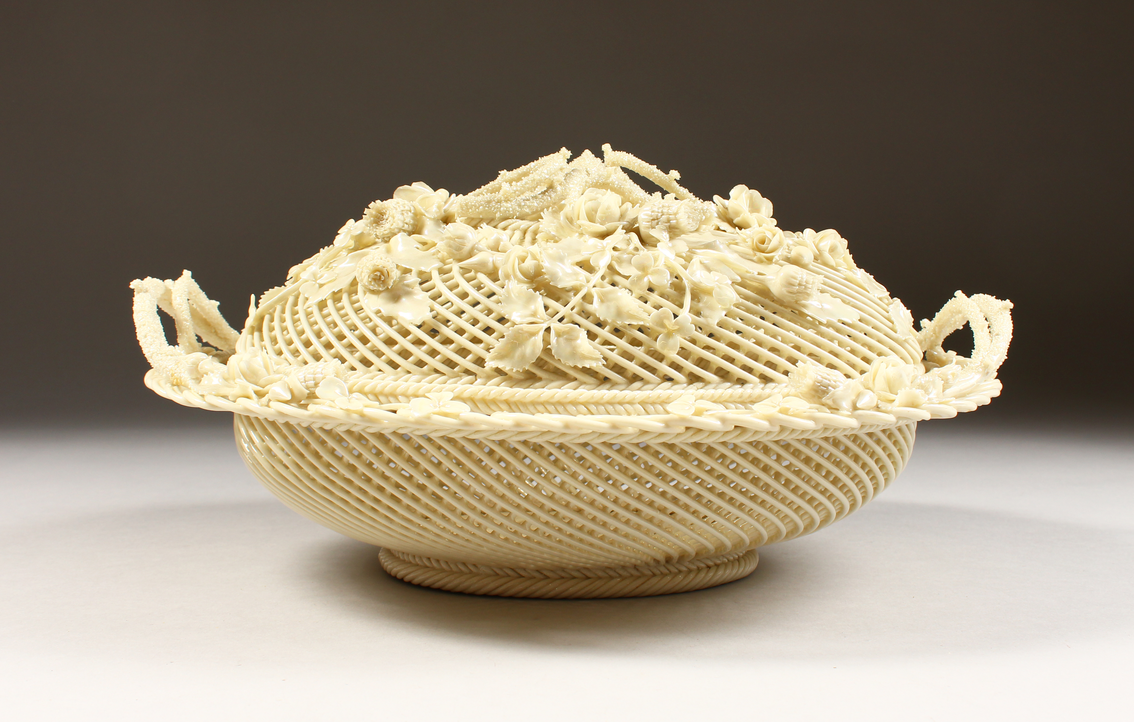 A Belleek oval lattice work basket and cover encrusted with shamrock/Auctioneers and Valuers