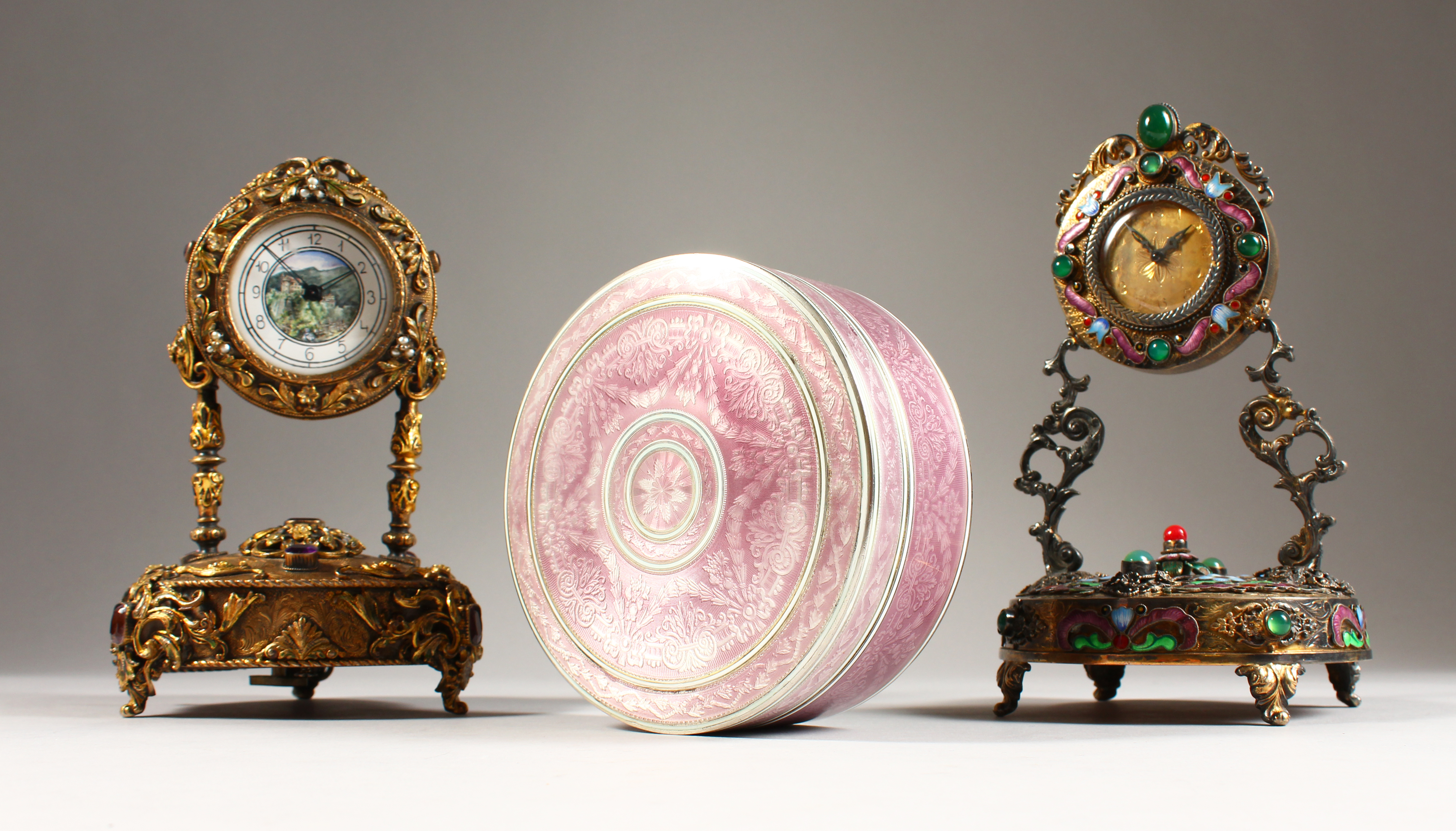 A Faberge circular box and two clocks set with precious stones/Auctioneers and Valuers